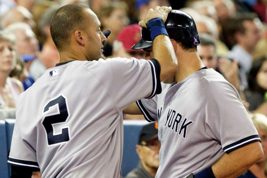 New York Yankees' Derek Jeter pats teammate Mark Teixeira on the helmet for hitting a solo home run off Toronto Blue Jays pitcher Steve Delabar during eighth-inning baseball game action in Toronto, Friday, Aug. 10, 2012. (AP Photo/The Canadian Press, Chris Young) Photo: Chris Young