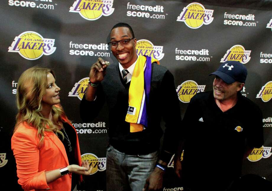Dwight Howard, center, is all smiles after finally getting his wish, a trade from the Orlando Magic to the Lakers, who are run by Jim Buss and his sister, Jeanie. Photo: Anne Cusack / Los Angeles Times