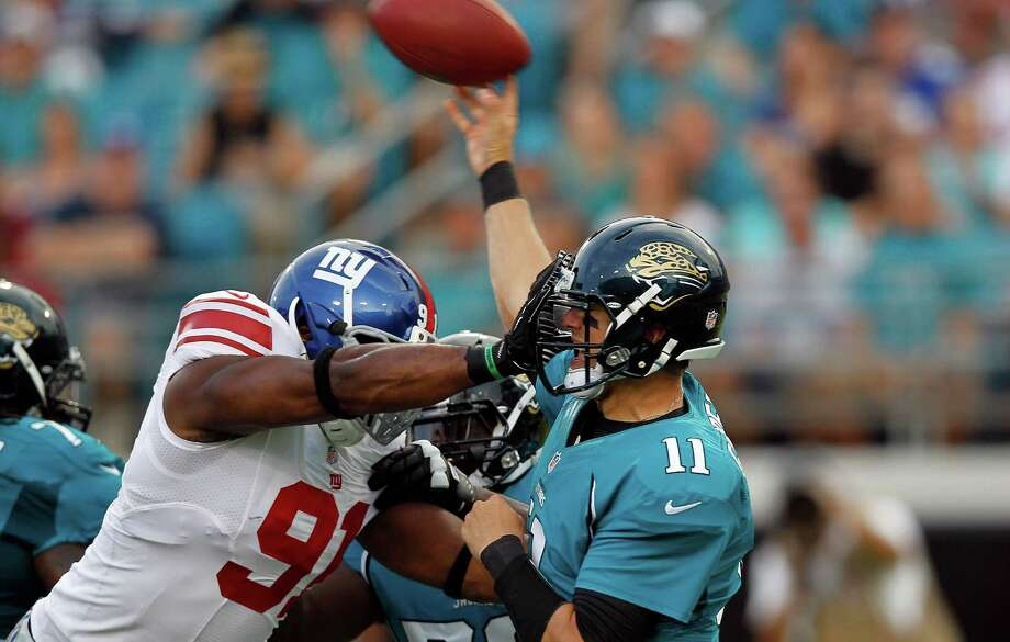 Jacksonville Jaguars quarterback Blaine Gabbert (11) is hit by New York Giants defensive end Justin Tuck (91) as he releases a pass in the first half of an NFL preseason football game Friday, Aug. 10, 2012, in Jacksonville, Fla. (AP Photo/John Bazemore) Photo: John Bazemore