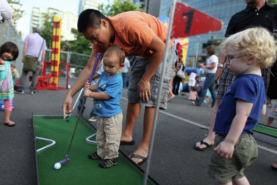 Sawyer Gee, 1, gets some golf instruction from his dad Lippman Gee in the kids' area. Photo: JOSHUA TRUJILLO / SEATTLEPI.COM