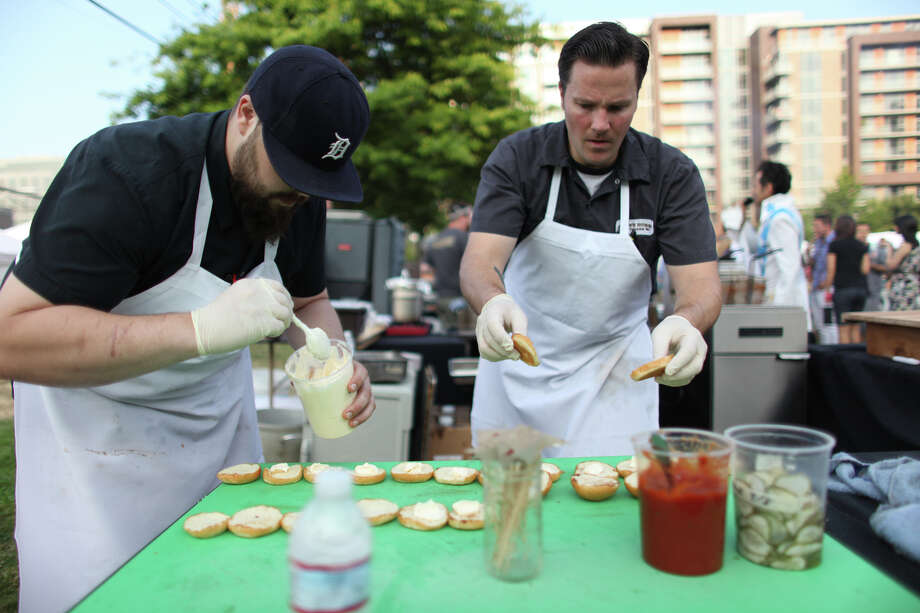 Aaron Wilcenski, left, and Brian Walczyk of Brave Horse Tavern work on their creations during the burger competition at the South Lake Union Block Party. Photo: JOSHUA TRUJILLO / SEATTLEPI.COM