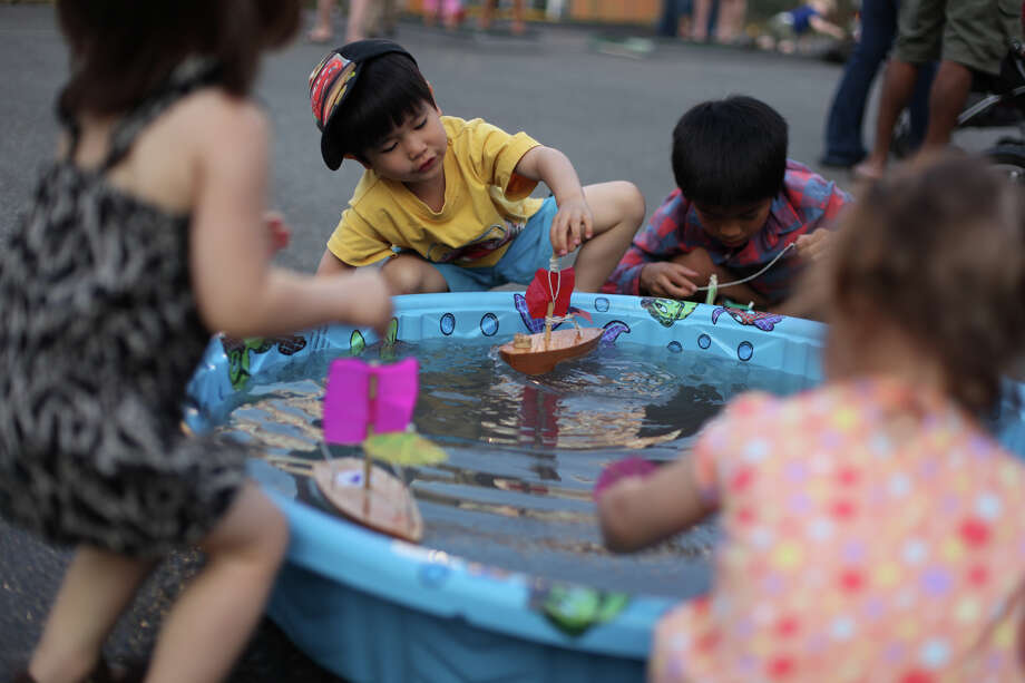 Gregory Chin, 4, center left, floats a wooden boat he made in the kids' area at the South Lake Union Block Party. Photo: JOSHUA TRUJILLO / SEATTLEPI.COM