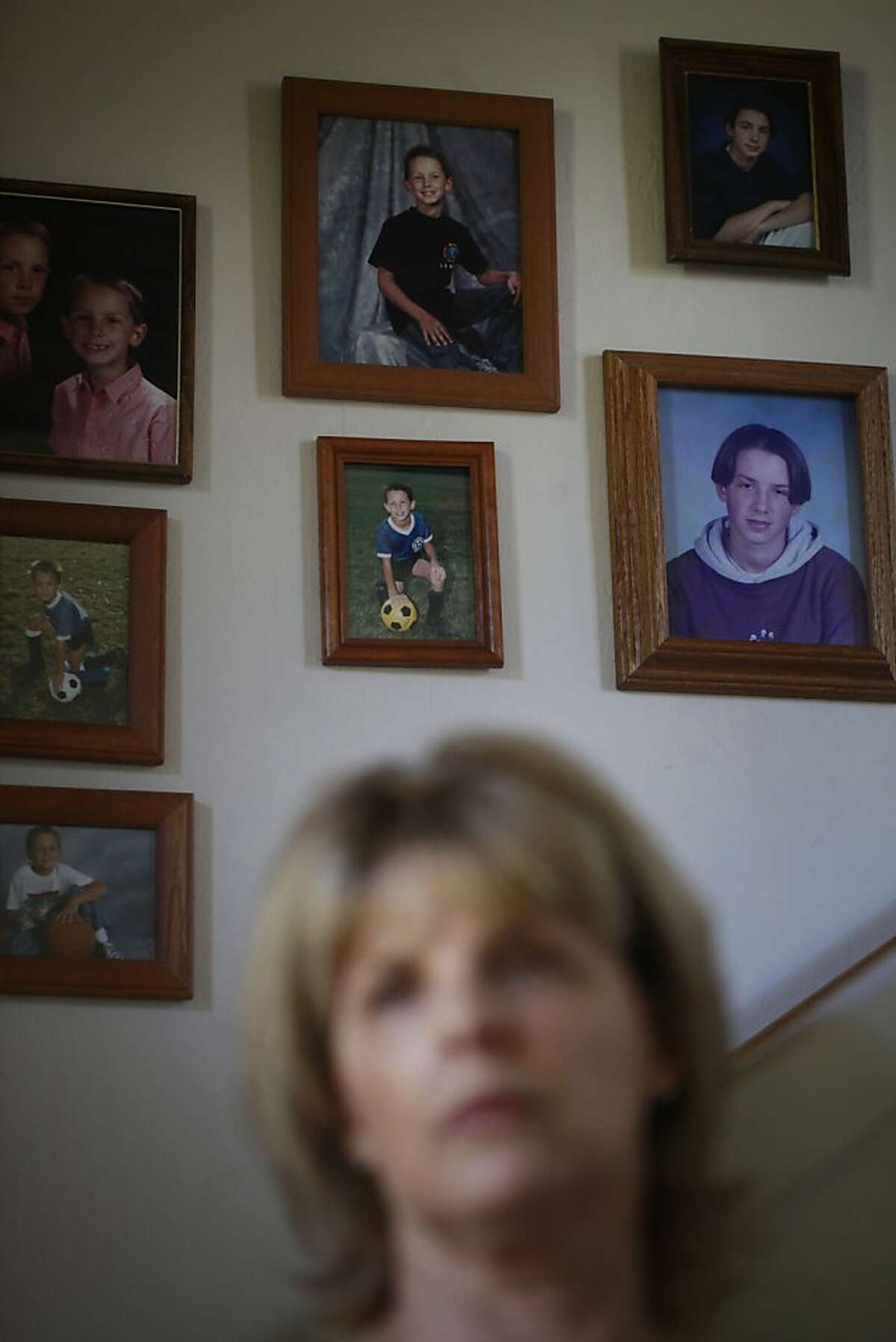 Standing in front of wall of photographs that predate her son's illness, Laura's Law supporter,Teresa Pasquini, whose 29-year-old son is at Napa State for treatment of schizophrenia, tells her store on July 10, 2012 in El Sobrante, Calif. She said dealing with her son's mental illness has taken all of her energy but she refuses to give up on him.