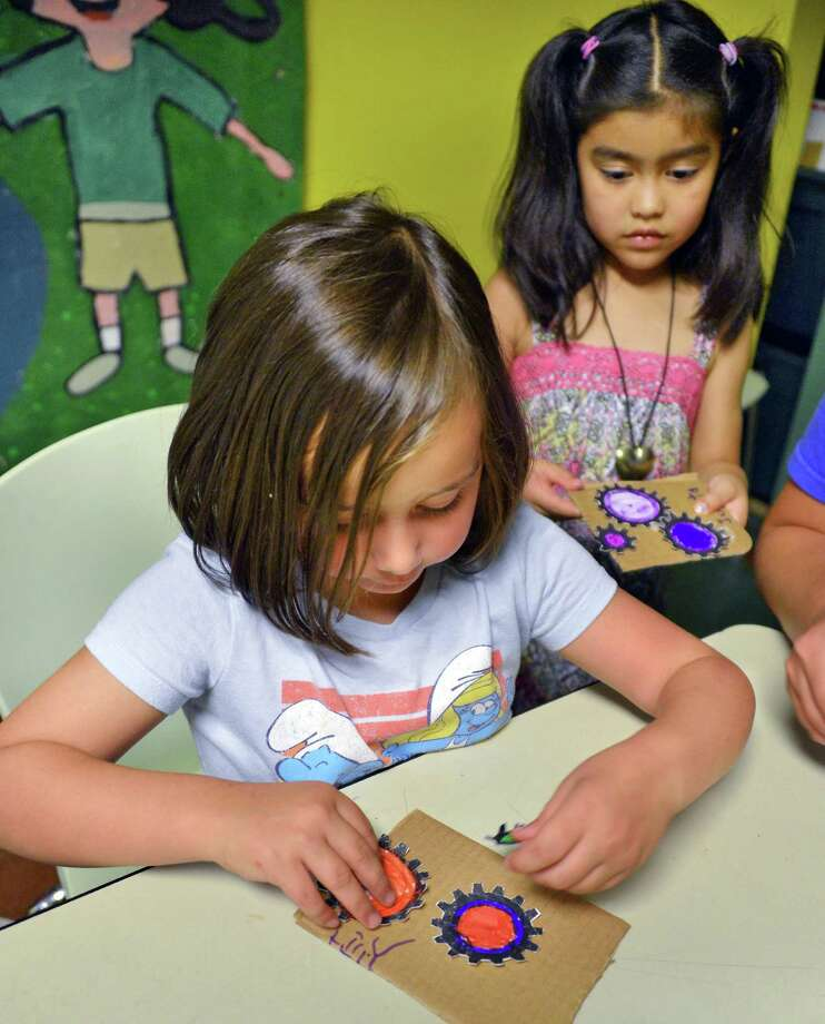 Lilly Gardell, 5, of Albany, left, and Julieta Gil-Marin work on a gears project during science and engineering 101 summer camp at the Children's Museum of Science and Technology in Troy Friday Aug. 10, 2012.  (John Carl D'Annibale / Times Union) Photo: John Carl D'Annibale / 00018805A