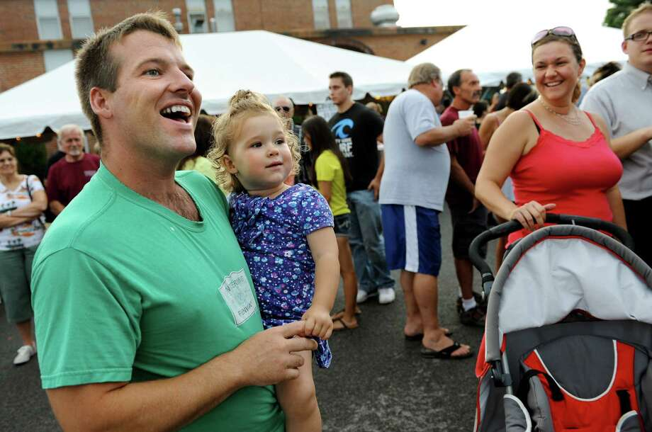 Sean Mullen of Rotterdam, left, swings to the music with his daughter, Emma, 2, during Festa on Friday, Aug. 10, 2012, at Our Lady Queen of Peace Church in Rotterdam, N.Y. The event features traditional Italian foods, baked goods, Italian ice, rides for kids and live music. It continues Saturday from 5 to 11 p.m. and Sunday from 3 to 9 p.m. (Cindy Schultz / Times Union) Photo: Cindy Schultz / 00018804A