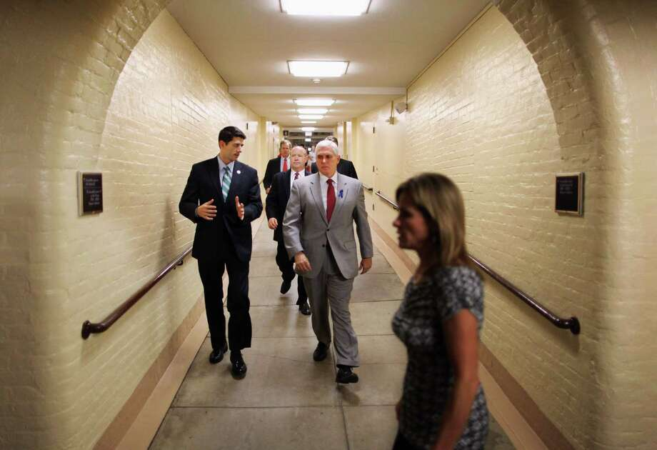 WASHINGTON, DC - JULY 25:  House Budget Committee Chairman Paul Ryan (R-WI) (L) talks with U.S. Rep. Mike Pence (R-IN) as they head to a Republican conference meeting in the basement of the U.S. Capitol July 25, 2011 in Washington, DC. Both Democrats and Republicans in the House and Senate have started the week with a series of caucus meetings to talk about the ongoing budget and debt ceiling negotiations.  (Photo by Chip Somodevilla/Getty Images) Photo: Chip Somodevilla, Getty Images / 2011 Getty Images