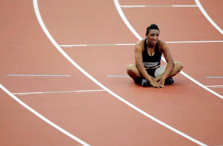 "In this Sunday, Aug. 5, 2012 photo, Syria's Ghfran Almouhamad sits in her lane after a women's 400-meter hurdles qualifying race during the athletics in the Olympic Stadium at the 2012 Summer Olympics, London. The IOC said Saturday Aug. 11, 2012 that 400-meter hurdler Almouhamad tested positive for the banned stimulant methylhexaneamine on Aug. 3. The backup ""B"" sample confirmed the positive finding. The 23-year-old athlete finished eighth and last in her first-round heat on Aug. 5. The IOC said she has been disqualified and stripped of her Olympic accreditation. (AP Photo/Matt Slocum) Photo: Matt Slocum / AP"