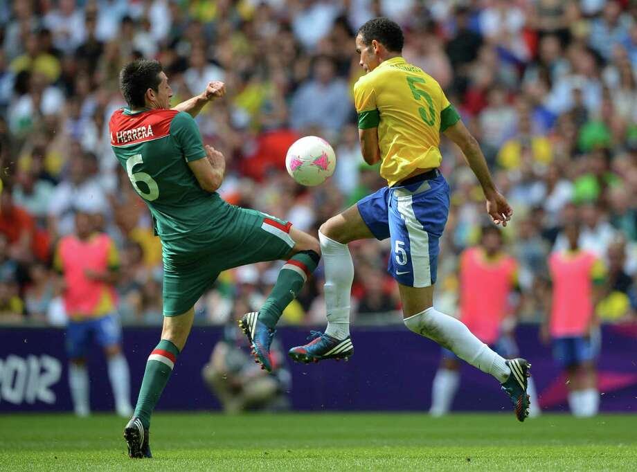 LONDON, ENGLAND - AUGUST 11:  Hector Herrera of Mexico (L) and Sandro of Brazil battle for the ball during the Men's Football Final between Brazil and Mexico on Day 15 of the London 2012 Olympic Games at Wembley Stadium on August 11, 2012 in London, England. Photo: Jeff J Mitchell, Getty Images / 2012 Getty Images