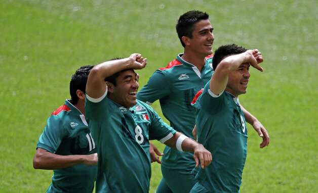 Mexico's Javier Aquino (11), Marco Fabian (8), Darvin Chavez (5) and Oribe Peralta (9) celebrate during the men's soccer final against Brazil at the 2012 Summer Olympics, Saturday, Aug. 11, 2012, in London. (AP Photo/Andrew Medichini) Photo: Andrew Medichini / AP