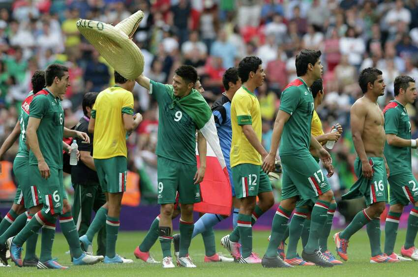 Mexico's Oribe Peralta (9) holds a hat to place on teammate Hector Herrera (6) as the team celebrates winning the gold medal in the men's soccer final against Brazil at the 2012 Summer Olympics, Saturday, Aug. 11, 2012, in London.