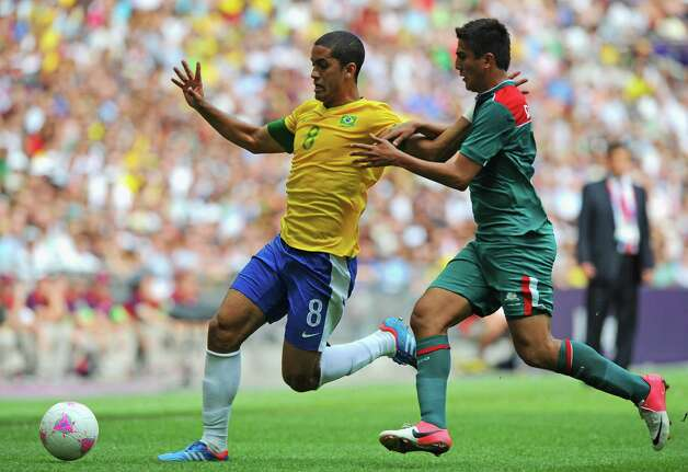 LONDON, ENGLAND - AUGUST 11:  Romulo of Brazil (L) is challenged by Darvin Chavez of Mexico during the Men's Football Final between Brazil and Mexico on Day 15 of the London 2012 Olympic Games at Wembley Stadium on August 11, 2012 in London, England. Photo: Michael Regan, Getty Images / 2012 Getty Images