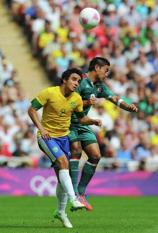 LONDON, ENGLAND - AUGUST 11:  Rafael of Brazil (L) battles for the ball with Marco Fabian of Mexico during the Men's Football Final between Brazil and Mexico on Day 15 of the London 2012 Olympic Games at Wembley Stadium on August 11, 2012 in London, England. Photo: Michael Regan, Getty Images / 2012 Getty Images