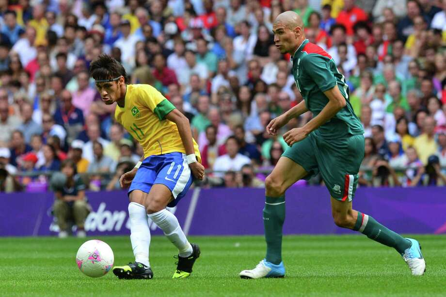 Brazil's forward Neymar (L) is challenged for the ball by Mexico's midfielder Jorge Enriquez in the men's football final match between Brazil and Mexico at Wembley stadium during the London Olympic Games on August 11, 2012.     AFP PHOTO / LUIS ACOSTALUIS ACOSTA/AFP/GettyImages Photo: LUIS ACOSTA, AFP/Getty Images / AFP