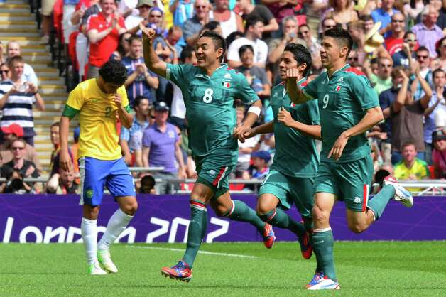 Mexico's forward Oribe Peralta (R) celebrates with teammates Mexico's midfielder Javier Aquino (2ndR) and Mexico's forward Marco Fabian after scoring the opening goal against Brazil in the men's football final match between Brazil and Mexico at the Millenium stadium in Cardiff during the London Olympic Games on August 11, 2012.    AFP PHOTO / LUIS ACOSTALUIS ACOSTA/AFP/GettyImages Photo: LUIS ACOSTA, AFP/Getty Images / AFP
