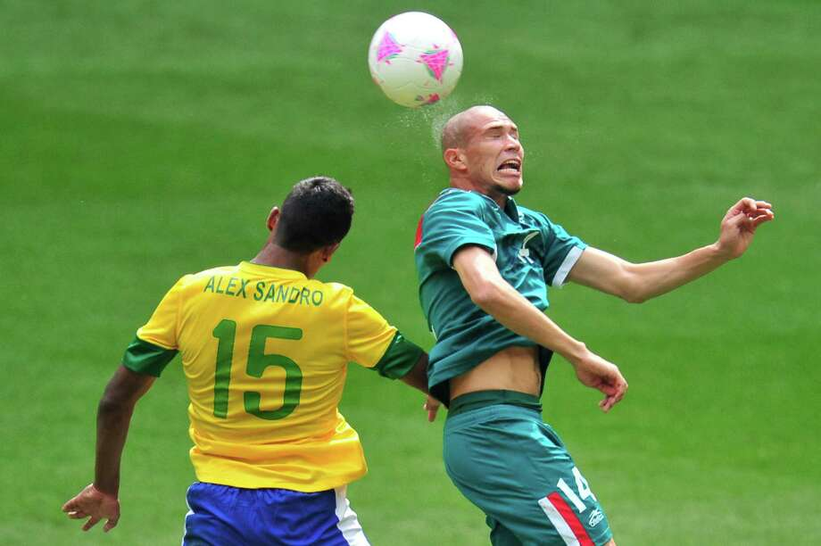 Mexico's midfielder Jorge Enriquez (R) heads the ball next to Brazil's defender Alex Sandro in the men's football final match between Brazil and Mexico at Wembley stadium in London during the London Olympic Games on August 11, 2012.    AFP PHOTO / GLYN KIRKGLYN KIRK/AFP/GettyImages Photo: GLYN KIRK, AFP/Getty Images / AFP