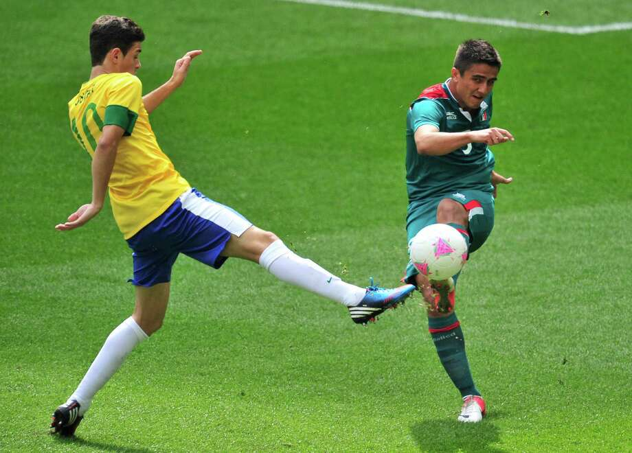 Mexico's defender Darvin Chavez (R) fights for the ball with Brazil's midfielder Oscar in the men's football final match between Brazil and Mexico at Wembley stadium in London during the London Olympic Games on August 11, 2012.    AFP PHOTO / GLYN KIRKGLYN KIRK/AFP/GettyImages Photo: GLYN KIRK, AFP/Getty Images / AFP