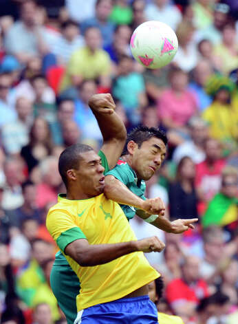 Mexico's forward Marco Fabian (R) and Brazil's defender Juan Jesus (L) jump for the ball during the men's football final match between Brazil and Mexico at the Wembley stadium in London during the London Olympic Games on August 11, 2012.    AFP PHOTO / DANIEL GARCIADANIEL GARCIA/AFP/GettyImages Photo: DANIEL GARCIA, AFP/Getty Images / AFP