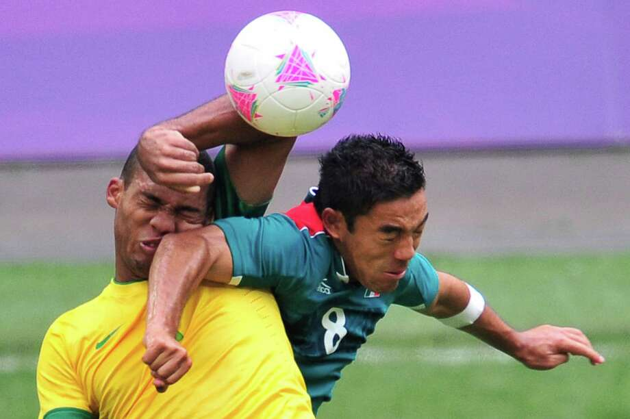 Brazil's defender Juan Jesus (L) fights for the ball with Mexico's forward Marco Fabian in the men's football final match between Brazil and Mexico at Wembley stadium in London during the London Olympic Games on August 11, 2012.    AFP PHOTO / GLYN KIRKGLYN KIRK/AFP/GettyImages Photo: GLYN KIRK, AFP/Getty Images / AFP