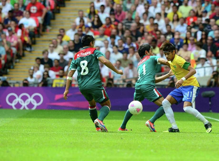 Brazil's forward Neymar (R) vies for the ball with Mexico's midfielder Javier Aquino (C) and Mexico's forward Marco Fabian (L) during the men's football final match between Brazil and Mexico at the Wembley stadium in London during the London Olympic Games on August 11, 2012.    AFP PHOTO / DANIEL GARCIADANIEL GARCIA/AFP/GettyImages Photo: DANIEL GARCIA, AFP/Getty Images / AFP