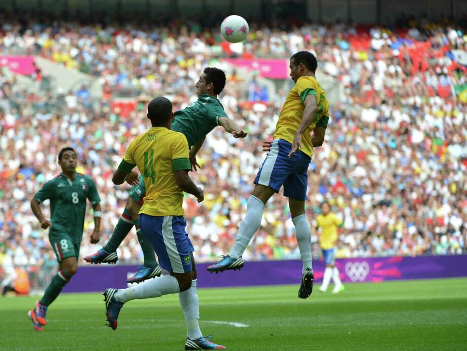 Mexico's midfielder Hector Herrera (C) and Brazil's midfielder Sandro (R) jump fpr the ball during the men's football final match between Brazil and Mexico at the Wembley stadium in London during the London Olympic Games on August 11, 2012.     AFP PHOTO / KHALED DESOUKIKHALED DESOUKI/AFP/GettyImages Photo: KHALED DESOUKI, AFP/Getty Images / AFP