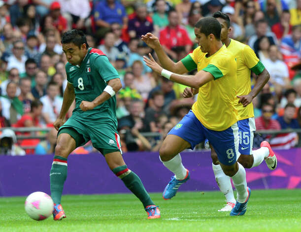 Mexico's forward Marco Fabian (L) runs with the ball followed by Brazil's defender Romulo (C) and Brazil's defender Alex Sandro during the men's football final match between Brazil and Mexico at the Wembley stadium in London during the London Olympic Games on August 11, 2012.     AFP PHOTO / DANIEL GARCIADANIEL GARCIA/AFP/GettyImages Photo: DANIEL GARCIA, AFP/Getty Images / AFP