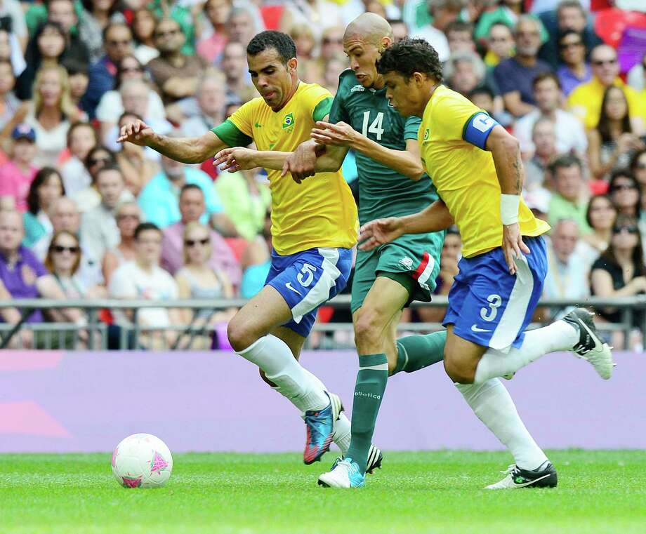 Mexico's midfielder Jorge Enriquez (C) vies for the ball with Brazil's midfielder Sandro (L) and Brazil's defender Thiago Silva (R) during the men's football final match between Brazil and Mexico at the Wembley stadium in London during the London Olympic Games on August 11, 2012.  AFP PHOTO / DANIEL GARCIADANIEL GARCIA/AFP/GettyImages Photo: DANIEL GARCIA, AFP/Getty Images / AFP