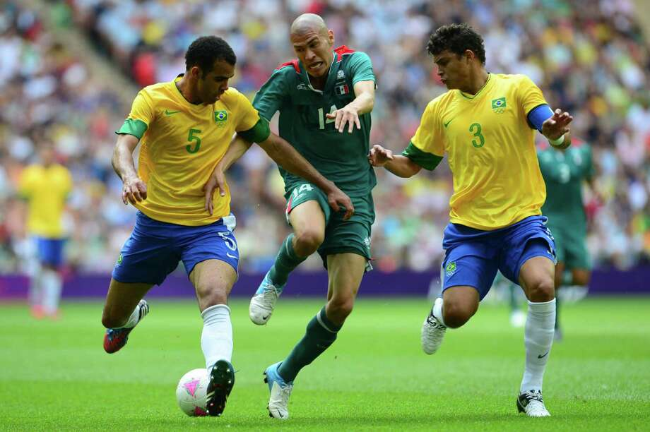 Mexico's midfielder Jorge Enriquez (C) fights for the ball with Brazil's midfielder Sandro (L) and Brazil's defender Thiago Silva in the men's football final match between Brazil and Mexico at Wembley stadium during the London Olympic Games on August 11, 2012.      AFP PHOTO / MARTIN BERNETTIMARTIN BERNETTI/AFP/GettyImages Photo: MARTIN BERNETTI, AFP/Getty Images / AFP