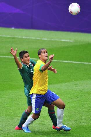 Brazil's defender Romulo (R) is challenged by Mexico's defender Darvin Chavez in the men's football final match between Brazil and Mexico at Wembley stadium during the London Olympic Games on August 11, 2012.      AFP PHOTO / GLYN KIRKGLYN KIRK/AFP/GettyImages Photo: GLYN KIRK, AFP/Getty Images / AFP