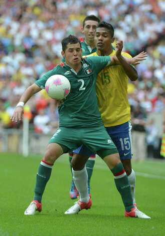 Brazil's defender Alex Sandro (R) and Mexico's defender Israel Jimenez (L) vie for the ball during the men's football final match between Brazil and Mexico at the Wembley stadium in London during the London Olympic Games on August 11, 2012.   AFP PHOTO / KHALED DESOUKIKHALED DESOUKI/AFP/GettyImages Photo: KHALED DESOUKI, AFP/Getty Images / AFP