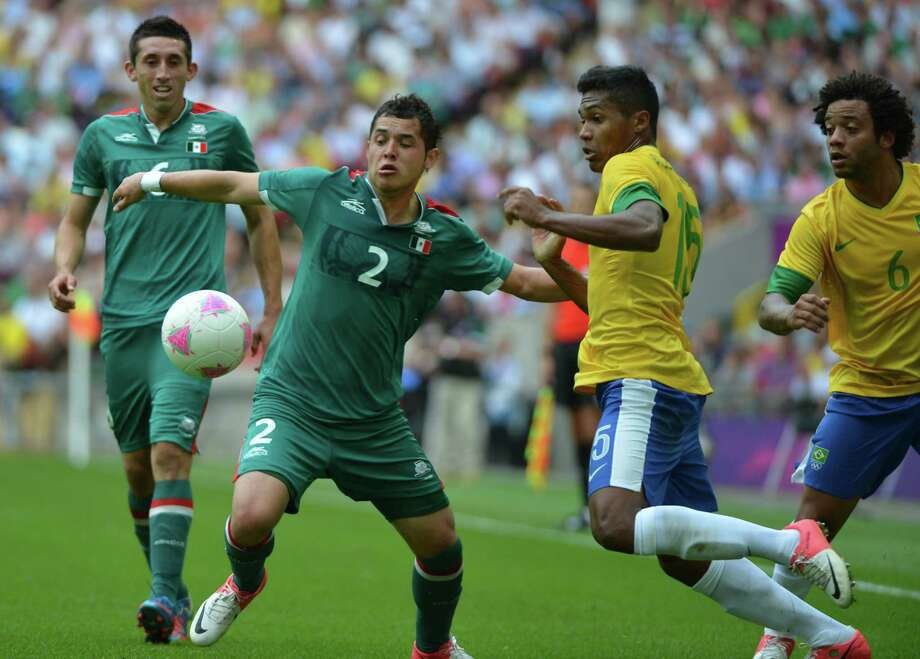 Brazil's defender Alex Sandro (2R) and Mexico's defender Israel Jimenez (2L) vie for the ball during the men's football final match between Brazil and Mexico at the Wembley stadium in London during the London Olympic Games on August 11, 2012.   AFP PHOTO / KHALED DESOUKIKHALED DESOUKI/AFP/GettyImages Photo: KHALED DESOUKI, AFP/Getty Images / AFP