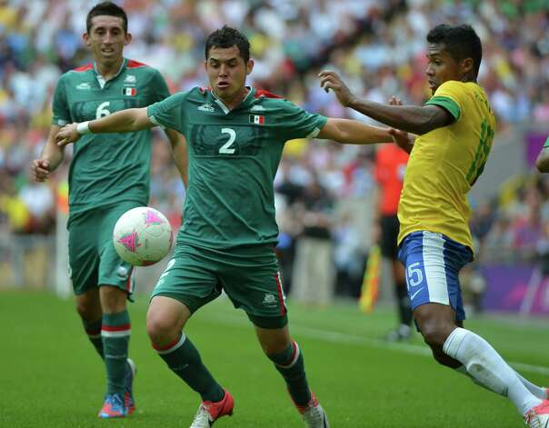 Brazil's defender Alex Sandro (R) and Mexico's defender Israel Jimenez (2L) vie for the ball during the men's football final match between Brazil and Mexico at the Wembley stadium in London during the London Olympic Games on August 11, 2012.   AFP PHOTO / KHALED DESOUKIKHALED DESOUKI/AFP/GettyImages Photo: KHALED DESOUKI, AFP/Getty Images / AFP