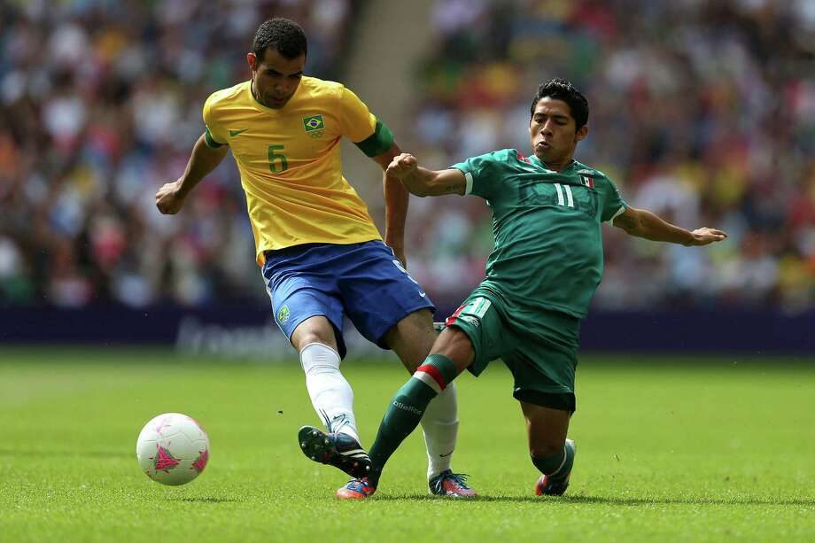 LONDON, ENGLAND - AUGUST 11:  Sandro of Brazil (L) is tackled by Javier Aquino of Mexico during the Men's Football Final between Brazil and Mexico on Day 15 of the London 2012 Olympic Games at Wembley Stadium on August 11, 2012 in London, England. Photo: Julian Finney, Getty Images / 2012 Getty Images