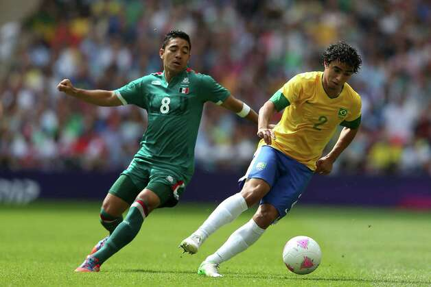 LONDON, ENGLAND - AUGUST 11:  Marco Fabian of Mexico in action against Rafael of Brazil (R) during the Men's Football Final between Brazil and Mexico on Day 15 of the London 2012 Olympic Games at Wembley Stadium on August 11, 2012 in London, England. Photo: Julian Finney, Getty Images / 2012 Getty Images