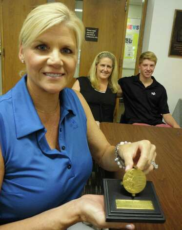 Sheila Stolarski of Weston holds the actual Olympic gold medal that her late mother Marie Corridon Mortell, of Norwalk, won during the 1948 Summer Olympic Games in London. Behind her is her sister Kate Mortell and her son Edward Stolarski, 14. A replica of the medal is on display at the Norwalk YMCA. Photo: Meg Barone