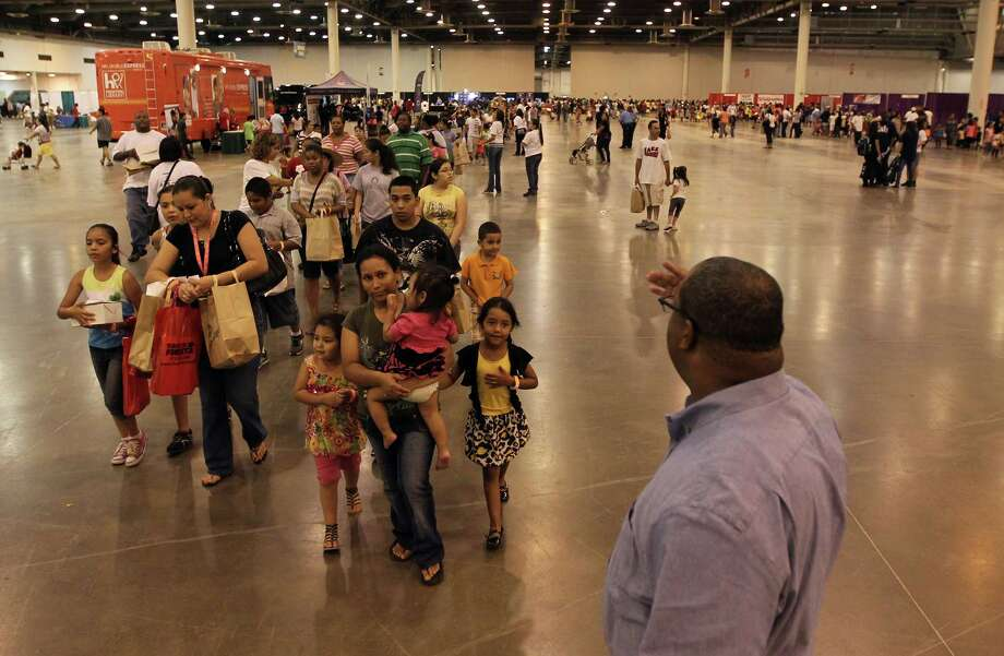 "Families form a line during the City of Houston & Houston Independent School District's ""Back to School Fest"" at Reliant Center Saturday, Aug. 11, 2012, in Houston. The event included backpacks, school supplies, groceries and immunizations to help families prepare for the start of the new school year. Photo: James Nielsen, Chronicle / © Houston Chronicle 2012"