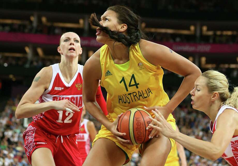 LONDON, ENGLAND - AUGUST 11:  Liz Cambage #14 of Australia attempts a shot in the first half against Irina Osipova #12 and Nadezhda Grishaeva #15 of Russia during the Women's Basketball Bronze Medal game on Day 15 of the London 2012 Olympic Games at North Greenwich Arena on August 11, 2012 in London, England. Photo: Christian Petersen, Getty Images / 2012 Getty Images