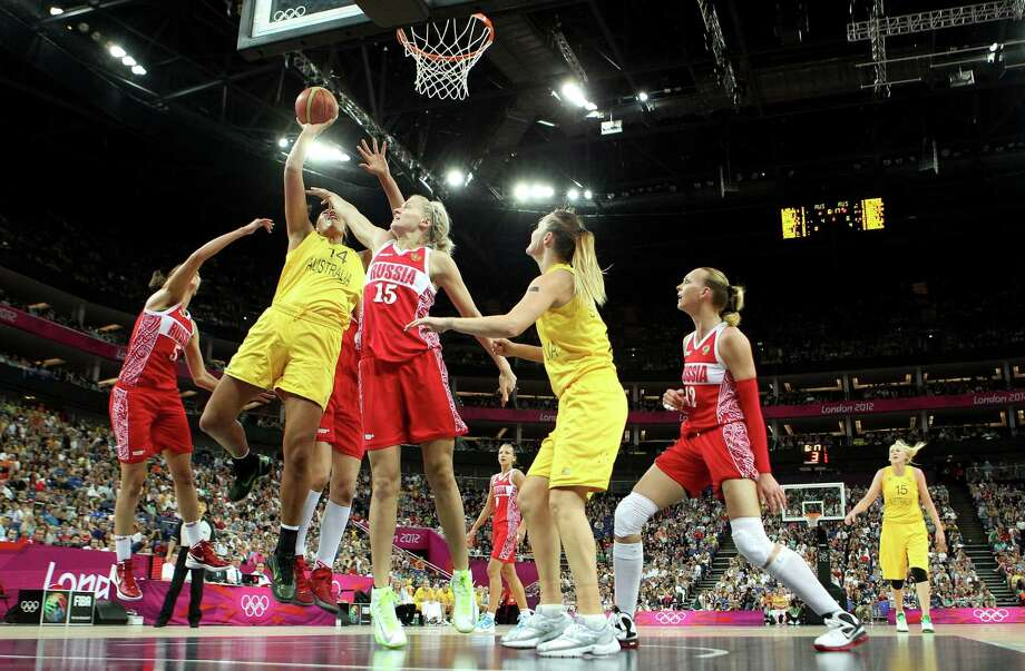 LONDON, ENGLAND - AUGUST 11:  Liz Cambage #14 of Australia attempts a shot against Nadezhda Grishaeva #15 and Evgeniya Belyakova #5 of Russia during the Women's Basketball Bronze Medal game on Day 15 of the London 2012 Olympic Games at North Greenwich Arena on August 11, 2012 in London, England. Photo: Christian Petersen, Getty Images / 2012 Getty Images