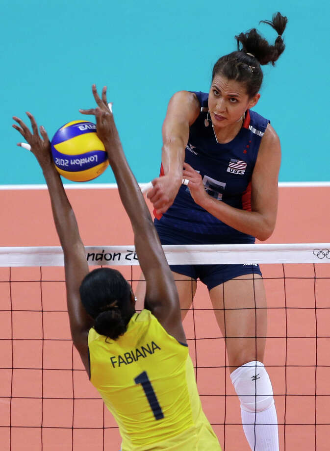 Brazil's Fabiana Claudino, bottom, blocks a spike from United States' Logan Tom during a women's gold medal volleyball match Saturday. (AP Photo/Jeff Roberson) Photo: Ap/getty