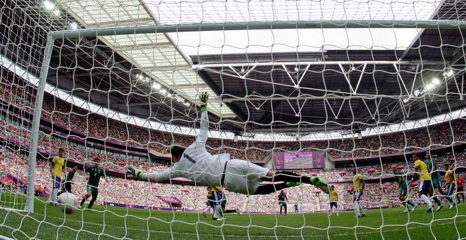 Brazil's Gabriel  can't stop Mexico's second goal by Oribe Peralta during the men's soccer final Saturday. (AP Photo/Jon Super) Photo: Ap/getty