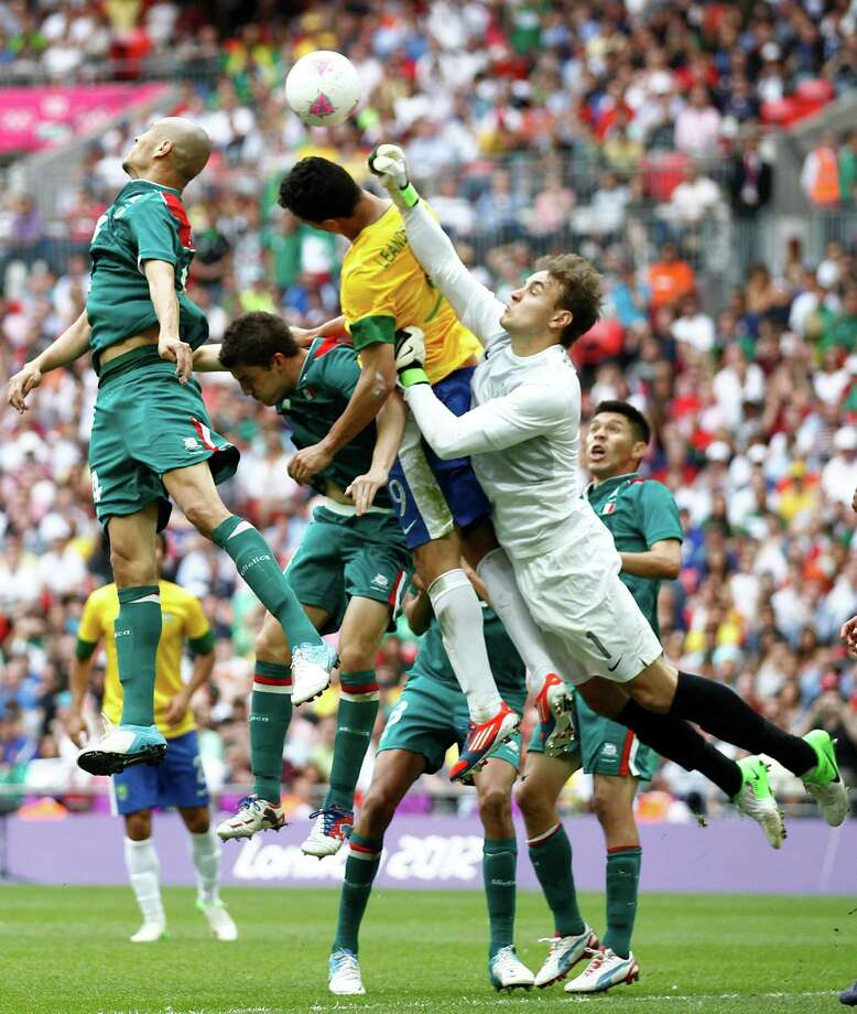 Brazil goalkeeper Gabriel, right, deflects a goal against Mexico during the men's soccer final Saturday. (AP Photo/Andrew Medichini) Photo: Ap/getty
