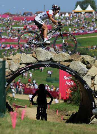 Elisabeth Osl of Austria rides under the bridge as Rie Katayama of Japan crosses over during the women's cross-country mountain bike race Saturday.  (Photo by Phil Walter/Getty Images) Photo: Phil Walter, Ap/getty / 2012 Getty Images