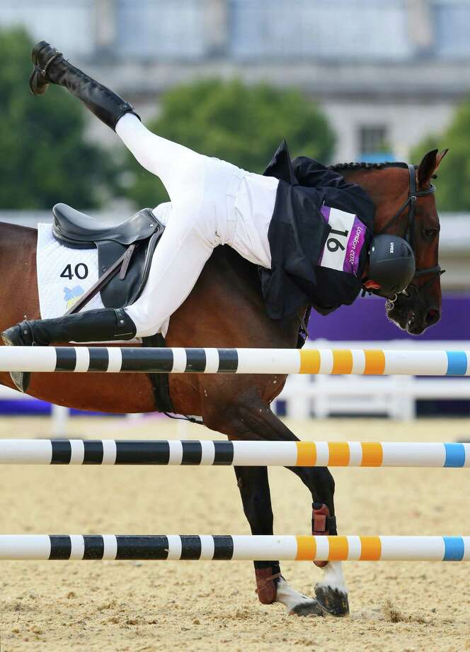 Dmytro Kirpulyanskyy of Ukraine falls from his saddle as he competes in the riding show jumping during the men's modern pentathlon Saturday.  (Photo by Alex Livesey/Getty Images) Photo: Alex Livesey, Ap/getty / 2012 Getty Images