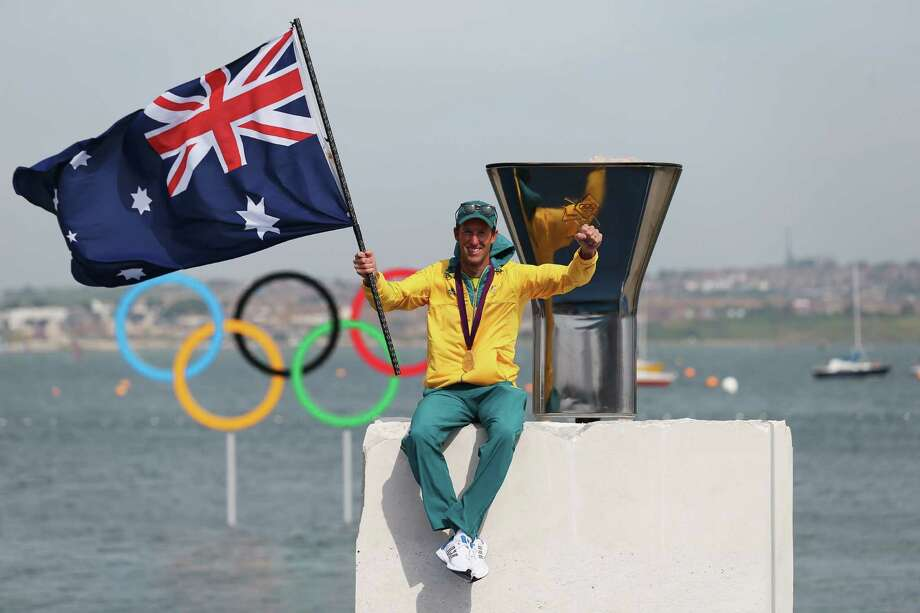 470 men's sailing gold medalist Malcolm Page of Australia poses in front of the Olympic cauldron on Saturday.  (Photo by Clive Mason/Getty Images) Photo: Clive Mason, Ap/getty / 2012 Getty Images