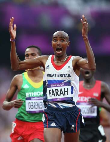 Mohamed Farah of Great Britain celebrates as he crosses the finish line to win gold ahead of Dejen Gebremeskel of Ethiopia and Thomas Pkemei Longosiwa of Kenya in the men's 5000m final Saturday.   (Photo by Michael Steele/Getty Images) Photo: Michael Steele, Ap/getty / 2012 Getty Images