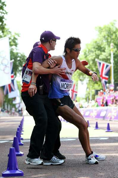 Koichiro Morioka of Japan gets help as he crosses the line during the men's 50km walk Saturday.  (Ph