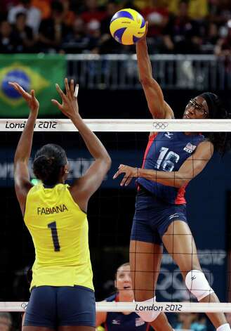 USA's Foluke Akinradewo (16) goes high in the air to spike over Brazil's Fabiana Claudino (1) during a women's volleyball gold medal match at the 2012 Summer Olympics Saturday, Aug. 11, 2012, in London. (AP Photo/Chris O'Meara) Photo: Chris O'Meara, Associated Press / AP