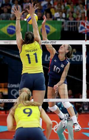 USA's Jordan Larson (10) goes up for a spike in front of Brazil's Tandara Caixeta (11) and Fernanda Ferreira (9) during a women's volleyball gold medal match at the 2012 Summer Olympics Saturday, Aug. 11, 2012, in London. (AP Photo/Chris O'Meara) Photo: Chris O'Meara, Associated Press / AP