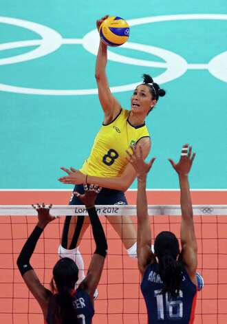LONDON, ENGLAND - AUGUST 11:  Jaqueline Carvalho #8 of Brazil spikes the ball against Foluke Akinradewo #16 and Destinee Hooker #19 of United States during the Women's Volleyball gold medal match on Day 15 of the London 2012 Olympic Games at Earls Court on August 10, 2012 in London, England. Photo: Ezra Shaw, Getty Images / 2012 Getty Images