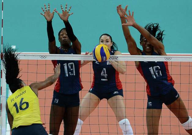 US Destinee Hooker (2-L), Lindsey Berg (2-R) and Foluke Akinradewo (R), block Brazil's Fernanda Rodrigues during the women's volleyball gold medal match of the London 2012 Olympics Games in London on August 11, 2012.    AFP PHOTO / FRANCISCO LEONGFRANCISCO LEONG/AFP/GettyImages Photo: FRANCISCO LEONG, AFP/Getty Images / AFP