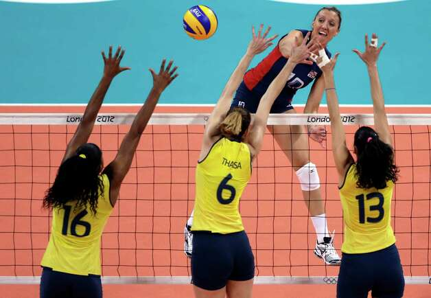United States' Jordan Larson, top, spikes the ball over Brazil's Fernanda Rodrigues (16), Thaisa Menezes (6) and Sheilla Castro during a women's gold medal volleyball match at the 2012 Summer Olympics, Saturday, Aug. 11, 2012, in London. (AP Photo/Jeff Roberson) Photo: Jeff Roberson, Associated Press / AP